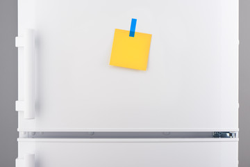 Blank yellow paper note and blue sticker on white refrigerator