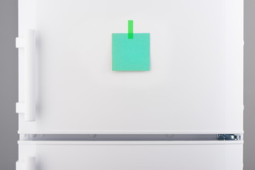 Blank green paper note attached by sticker on white refrigerator