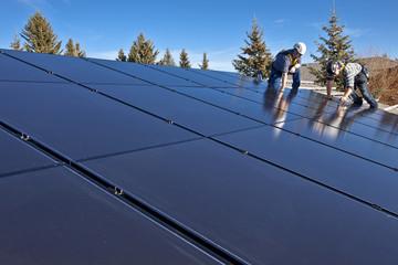 Two solar panel installers install solar panels on roof, Alberta foothills near Black Diamond, Alberta, Canada.