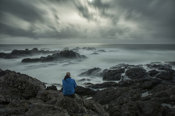 Long exposure of man sitting along the Wild Pacific Trail as the surf crashes over the rocky shoreline, Ucluelet, British Columbia, Canada
