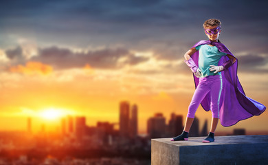 At sunset,little girl dressed as superhero watches over the city