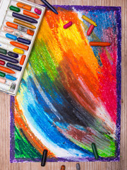 oil pastels drawing and crayons on wooden background