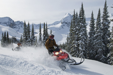 Two snowmobilers enjoy fresh powder in the Monashee mountains, in the North Thompson region near Valemount, British Columbia, Canada