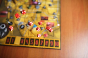 Several rolling red dice fall on a table with boardgame. Gameplay moments