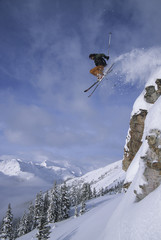 A skier jumping a cliff in the backcountry of Kickinghorse Resort, Purcell Range, Golden, British Columbia, Canada