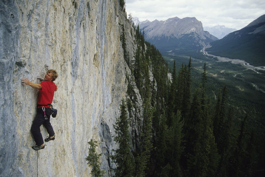 a young man leading up a route called Weapons of Mass Destruction in Spray Lakes, Alberta, Canada.
