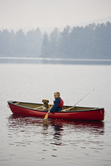 Young boy going fishing with dog in canoe on Source Lake, Algonquin Provincial Park, Ontario, Canada.