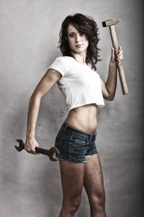 Sexy girl holding hammer and wrench spanner