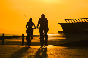 Couple riding bicycle at sunset sky, silhouette.