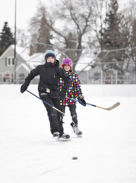 Boys playing ice hockey, on an outdoor neighborhood rink, Winnipeg, Manitoba, Canada