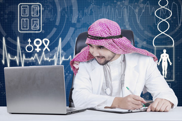 Arabian physician working with laptop