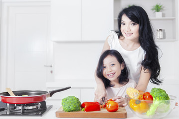 Happy woman and child cooking in kitchen