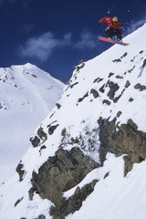 Young male snowboarder flying off large cliff at Lake Louise, Banff National Park, Alberta, Canada