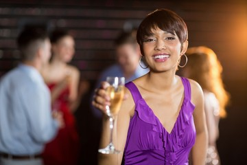 Portrait of young woman holding a glass of champagne