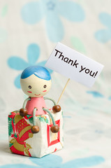 A doll and gift box with thank you card