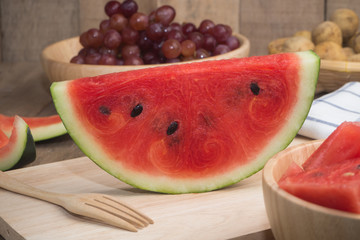 Kitchen table with Sliced of Watermelon on cutting board and grape fruit.