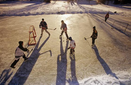 Boys playing hockey on outdoor rink, Winnipeg, Manitoba, Canada.