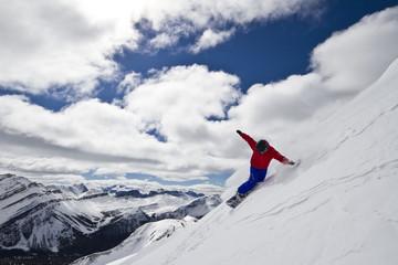 Young man snowboarding at Lake Louise Resort, Banff National Park, Alberta, Canada.