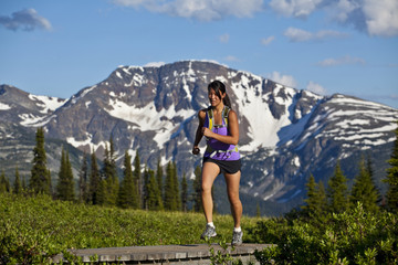 A young asian woman trailrunning beautiful singletrack in the the Trophy Mountains, Wells Grey Provincial Park, Clearwater, British Columbia, Canada