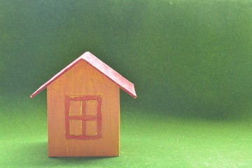 yellow model of house as symbol on green background