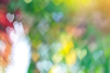 colorful of abstract blurred bokeh with heart shape background and golden sunlight effect.