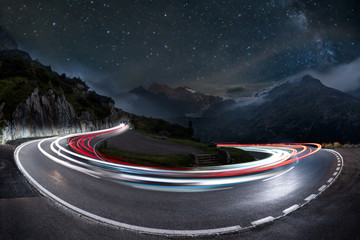Foto op Canvas Alpen light trails on a hairpin bend and milky way in the background. swiss alps pass road at night, starry sky with galaxy and car light trails