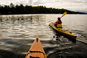 Young woman sea kayaking through Gull Narrows near Gravenhurst, Muskoka, Ontario, Canada.