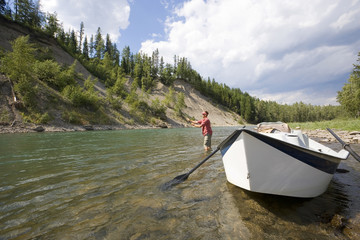 Young man fly fishing on the Elk River from a dory, Fernie, East Kootenays, British Columbia, Canada.