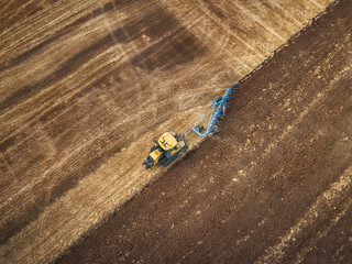 Wall Mural - Tractor cultivating field at autumn