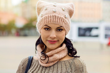 Woman's face in a knitted cap with a scarf, an autumn portrait