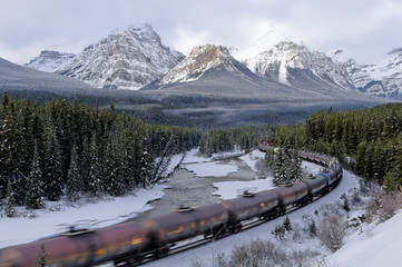 Train moving at Morant's curve, mountains in background