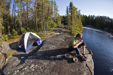 A young man canoeing and camping for 2 weeks in Wabakimi Provincial Park, Northern Ontario, Canada