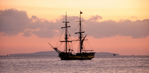 sailing ship at anchor, a calm sea and cloudless sky