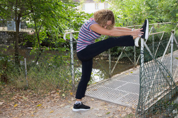 Blond woman middle aged stretching legs in a park