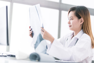 Woman Doctor Looking at X-Ray Radiography in patient's Room