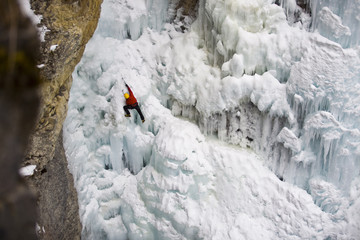 A male ice clmber tackles some steep ice in Johnstone  Canyon, Banff National Park, AB