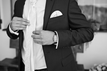 Close-up of man's hands holding white bow tie on the shirt