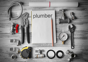Plumbing concept. Plumber tools with notebook on wooden textured background