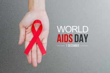 Obraz Female hands holding red ribbon HIV, AIDS awareness ribbon. World Aids Day concept. - fototapety do salonu