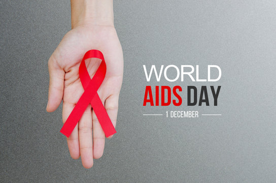 Female hands holding red ribbon HIV, AIDS awareness ribbon. World Aids Day concept.