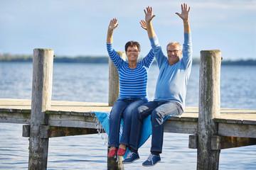 Lebensfreude - aktives Seniorenpaar sitzt am Steg am See
