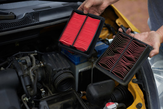 Comparison new and used air filter for car with engine bachground.