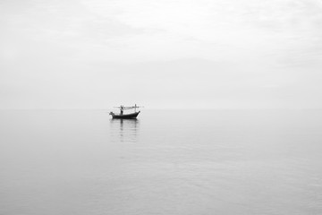 minimalism style picture,traditional fishing boat float on a peace surface wave of the sea,cloudy sky,high key picture