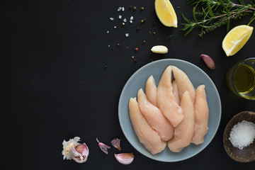 Fresh raw chicken tenders, lemon, garlic, rosemary, olive oil, pepper and salt on dark background