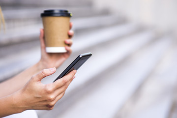Woman hold cup of coffee and smart phone on street, with space f