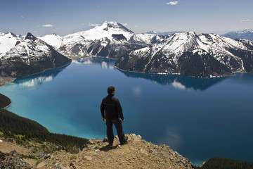 Hiker on top of Panorama Ridge over looking Garibaldi Lake in Garibaldi Provincial Park between the towns of Squamish and Whistler in British Columbia, Canada.
