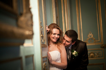 Bride leans to the old wall while groom kisses her shoulder tend