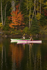 Two young women kayaking on Oxtongue Lake in autumn, Mukoka, Ontario, Canada.