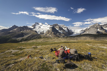 Two hikers relax overlooking Mount Athabasca from the summit of Wilcox Pass in Jasper National Park,Alberta, Canada. Model Released