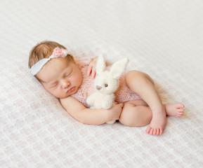 sleeping newborn girl with headband and holding toy
